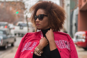 BBlack woman with natural hair wearing a black turtleneck, sunglasses and red satin Alabama jacket.